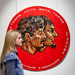 "© Licensed to London News Pictures. 03/06/2016. London, UK. A staff member stands with Komar and Melamid's ""Double Self-Portrait from the Sots Art Series"" (est. GBP 100,000-150,000), at a preview of Sotheby's Russian and contemporary central and eastern European art sale which takes place in London on 7 June. Photo credit : Stephen Chung/LNP"