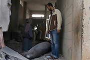 A Palestinian man examines a large bomb fragment that after exploding on a suspected tunnel house, landed in a room he uses as an animal pen following continued bombing by the Israeli Air Force along the Philadelphi corridor in Rafah Gaza January 16, 2009. The Israeli Defense Forces claim their sustained campaign has significantly degraded smuggling tunnels along  the corridor and the damaged the ability of HAMAS to smuggle weapons and cash into the Strip.