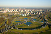 Nederland, Utrecht, Utrecht, 11-02-2008; Knooppunt Oudenrijn, ongelijkvloerse kruising van de snelwegen A12 (links - rechts) en A2, klaverblad met fly-overs (eigenlijk klaverturbine), het oudste verkeersknooppunt van Nederland; de foto is gemaakt in noordoostelijke richting, met zicht op Polder Papendorp met gelijknamig kantorenpark; over het Amsterdam-Rijnkanaal de Prins Clausbrug (ontwerp Ben van Berkel) met daarachter de hoogbouw van het Kanaleneiland; de waterpartijen van het verkeersplein vormen niet alleen een landschappelijke invulling voor de restruimte, maar dienen ook als bron voor bluswater ingeval calamiteiten; projectontwikkeling, projectontwikkelaars, vastgoed, planologie, kantoor, tuibrug, planologie, inrichting landschap, overhoeks..luchtfoto (toeslag); aerial photo (additional fee required); .foto Siebe Swart / photo Siebe Swart