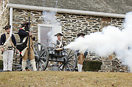 Newburgh, New York  - Revolutionary War reenactors in uniforms fire a cannon at Washington's Headquarters State Historic Site as part of George Washington's birthday celebration on Feb. 18, 2012. The reenactors are from John Lamb's Artillery Company. Their cannon is modeled on the British three-pounder field piece. Hasbrouck House, the longest-serving headquarters of Washington during the American Revolution, is in the background.