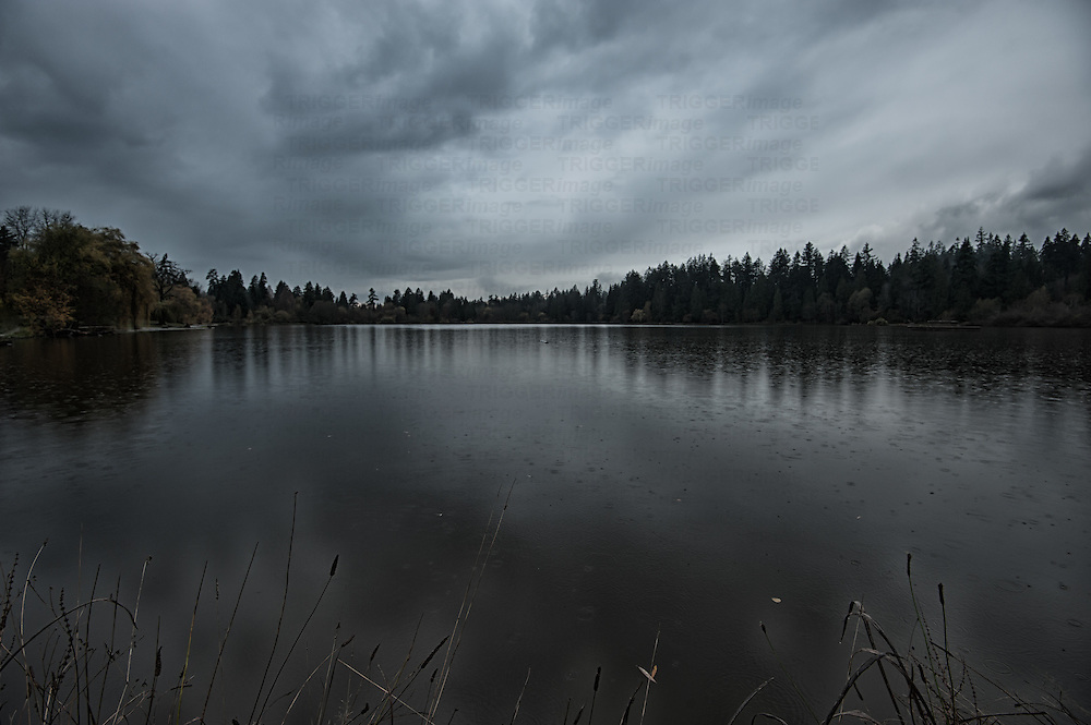 Rain drops and dramatic clouds over a lagoon on a dark November day in Canada.