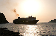 A ferry in silhouette at sunset arriving in Kamares, Sifnos, The Cyclades, Greek Islands, Greece, Europe