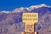 Sign at Furnace Creek Inn under snowy Telescope Peak, Death Valley National Park. California