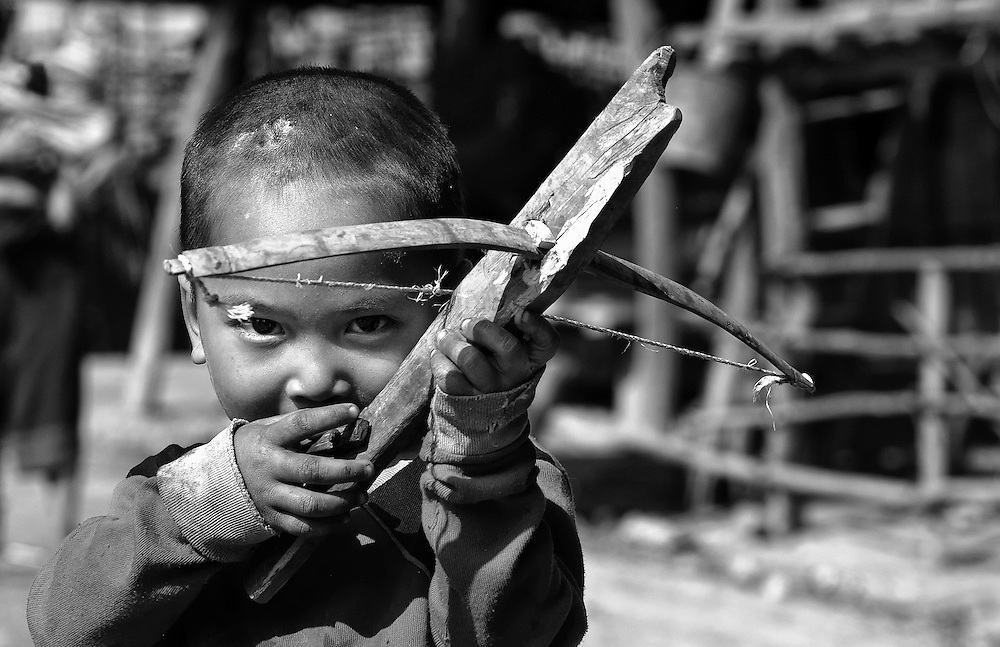 An Akha boy from Luang Namtha, Laos developes hunting skills with a crossbow.