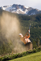 A male golfer pitches out of the sand on the Whistler Golf Course, Whistler, BC Canada with Whistler Mountain in the background.
