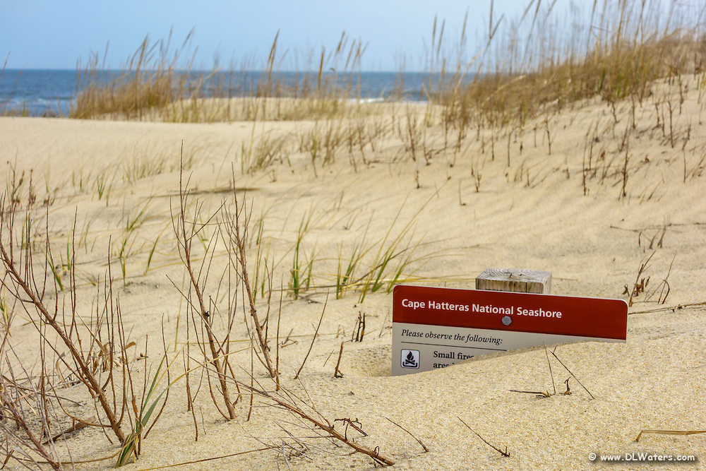 Cape Hatteras National Seashore sign buried in the dunes.