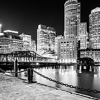 Boston skyline and Boston Harbor at night black and white photo. Includes the Boston Harborwalk waterfront, downtown Boston skyscrapers and Northern Avenue Bridge.