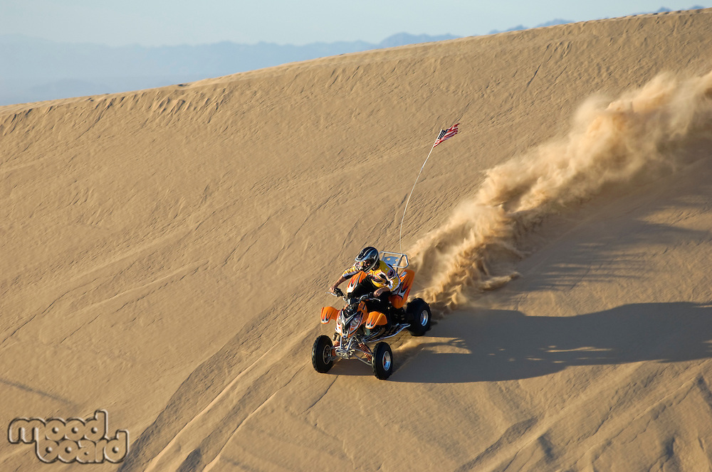 Young Man Riding ATV Over Sand Dune