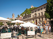 People in tourist cafe in Plaza Nueva, Granada, Spain looking up at part of the Alhambra on a hill top.