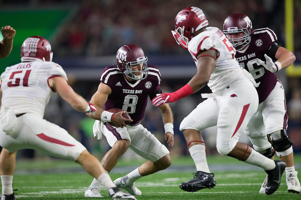 Texas A&M's quarterback Trevor Knight (8) looks for running room against Arkansas' defenders during the first quarter of an NCAA college football game Saturday, Sept. 24, 2016, in Arlington, Texas. (The Eagle/Sam Craft)