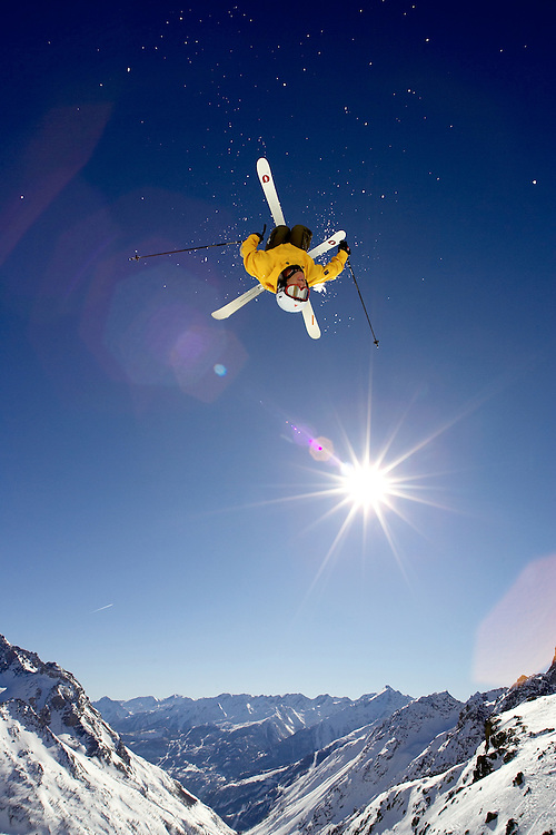 Skier jumping off rock on mountainside, Serre Chevalier Valley, France