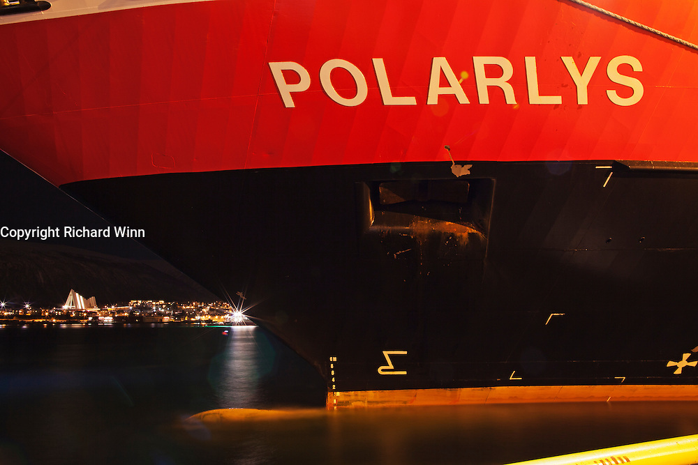 """View of the bow of the Hurtigruten ship """"Polarlys"""" (Polar Lights), framing the Ishvaskatedralen or the Arctic Church, across the fjord in Tromsdalen, photographed at night."""