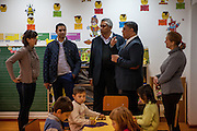 Roma activists Marius Tudor (2nd left), Marian Daragiuin (2nd right) and Gheorghe Tudor (3rd left) with two kindergarteners and a group of children at the local kindergarten in Marginenii de Jos.