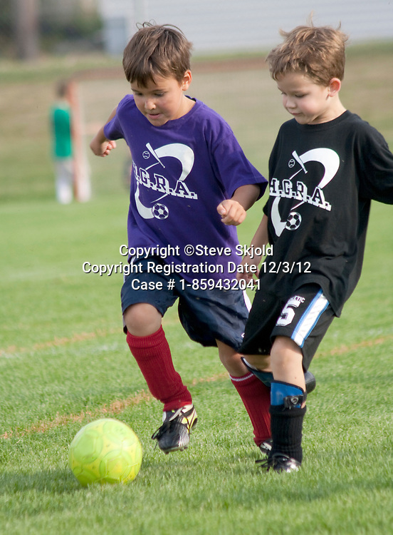 Two soccer player boys age 7 kicking to control the ball. Carondelet Field by Expo School St Paul Minnesota MN USA
