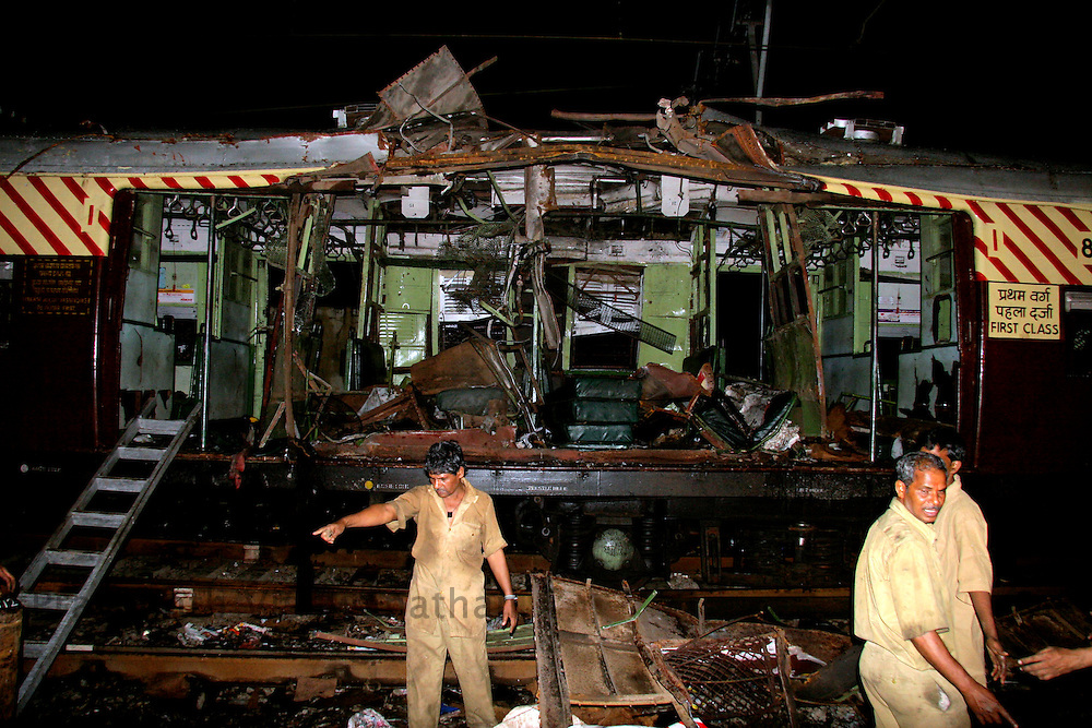 Workers clear the debris after a bomb blast in a train in Mumbai July 11, 2006.