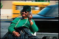 An African american woman relaxin on a garden chair in a street in Harlem in New York. May 2001
