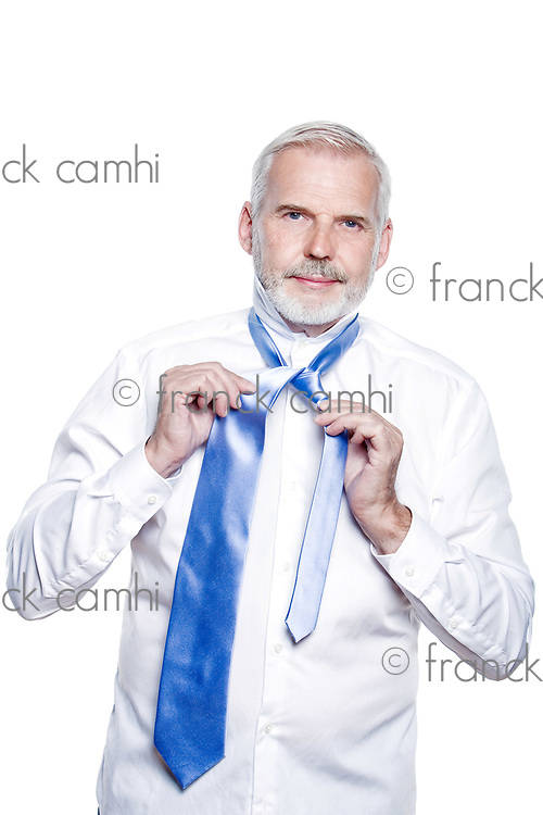 windsor necktie lesson doing by an handsome man senior getting dressed on isolated white background