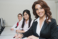 Cheerful Multi Racial Businesswomen Sitting at Desk