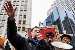 © Licensed to London News Pictures. 31/12/2016. Chicago, USA. Jesse Jackson (R) joins a Peace March, organised by Father Michael Pfleger (L) and builder of the crosses, Greg Zanis (R), taking place down Chicago's Magnificent Mile, Michigan Avenue, to honour the survivors and victims of the city's escalating gun violence.  Marchers carry a 2-foot-tall white wooden cross, each bearing the name of a person killed by gun violence in 2016.  With over 4,300 shootings and more than 750 people killed in 2016, these are the highest totals for 20 years and more than any other large U.S. city in 2016, according to news reports. Photo credit : Stephen Chung/LNP