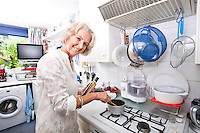 Portrait of happy senior woman preparing food in domestic kitchen