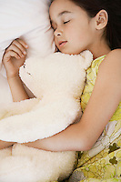 Girl cuddling teddy asleep on bed