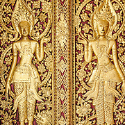Intricate carvings in the door at Wat Mai Suwannaphumaham.  Wat Mai, as it is often known, is a Buddhist temple in Luang Prabang, Laos, located near the Royal Palace Museum. It was built in the 18th century and is one of the most richly decorated Wats in Luang Prabang.
