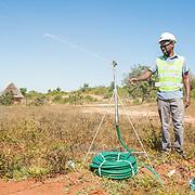 CAPTION: Tsungai checks a sprinkler that is part of the Kufandada River Protection and Irrigation Scheme Project. LOCATION: Bikita District, Masvingo Province, Zimbabwe. INDIVIDUAL(S) PHOTOGRAPHED: Tsungai Mavambe.
