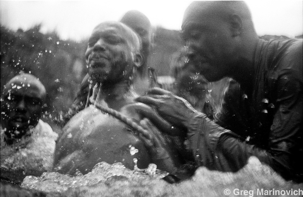Members of one of the many Africanist Zioni church/sect mebers purify themselves in a  Soweto Stream to mark the start of the new year. South Africa. Photo Greg Marinovich