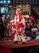 17 SEPTEMBER 2015 - BANGKOK, THAILAND:  A participant in the Santa pageant throws glitter while she walks the catwalk during the pageant at the World Santa Claus Congress. Twenty-six Santa Clauses from around the world are in Bangkok for the first World Santa Claus Congress. The World Santa Claus Congress has been an annual event in Denmark since 1957. This year's event, hosted by Snow Town, a theme park with a winter and snow theme, hosted the event. There were Santas from Japan, Hong Kong, the US, Canada, Germany, France and Denmark. They presented gifts to Thai children and judged a Santa pageant. Thailand, a Buddhist country, does not celebrate the religious aspects of Christmas, but Thais do celebrate the commercial aspects of the holiday.   PHOTO BY JACK KURTZ