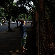 May 09, 2013 - Yangon, Myanmar: A local resident exercises in the early hours of the day, facing a fenced garden in central Yangon. (Paulo Nunes dos Santos/Polaris)
