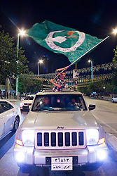© Licensed to London News Pictures. 27/04/2014. Sulaimaniya, Iraq. A supporter of the Patriotic Union of Kurdistan (PUK) political party waves his party's flag from the top of an off-road vehicle during celebrations in the lead up to the 2014 Iraqi parliamentary elections in Sulaimaniya, Iraqi-Kurdistan.<br /> <br /> Although banned in other parts of Iraqi-Kurdistan, the days leading up to an election in Sulaimaniya sees political supporters of all the three main parties parading up and down the main street of the city, waving flags, honking horns, letting off fireworks and firing pistols and rifles into the air.<br /> <br /> The period leading up to the elections, the fourth held since the 2003 coalition forces invasion, has already seen six polling stations in central Iraq hit by suicide bombers causing at least 27 deaths. Photo credit: Matt Cetti-Roberts/LNP