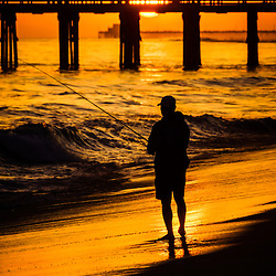 Orange County California sunset fishing picture. Man fishing during sunset along the Pacific Ocean shoreline om Balboa Peninsula in Newport Beach California. Balboa Pier and Newport Pier are in the background.