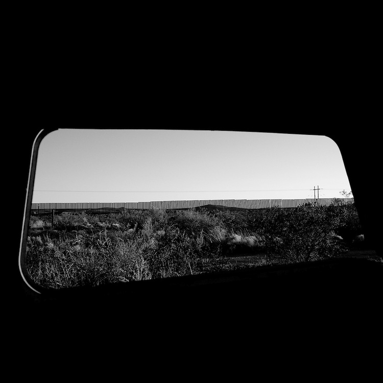 The fence marking the border between the United States and Mexico is seen through the back windshield of an abandoned car in Columbus, NM, on Tuesday, Jan. 29, 2008.