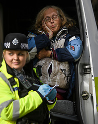 © Licensed to London News Pictures. 10/10/2019. London, UK. An Extinction Rebellion activists looks bored while being arrested for refusing to move from the roads around Trafalgar Square in Westminster, central London where campaigners have been demonstrating for a fourth day running. The climate change group have blockaded the Westminster area, demanding that the government takes immediate and decisive action on climate change. Photo credit: Ben Cawthra/LNP