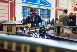 19/01/2018. London, UK. An enthusiast films on her mobile phone as a Gauge '1' steam locomotive passes through a miniature station at the London Model Engineering Exhibition at Alexandra Palace. Over 50 clubs and societies are exhibiting nearly 2,000 models constructed by their members. Photo credit: Rob Pinney