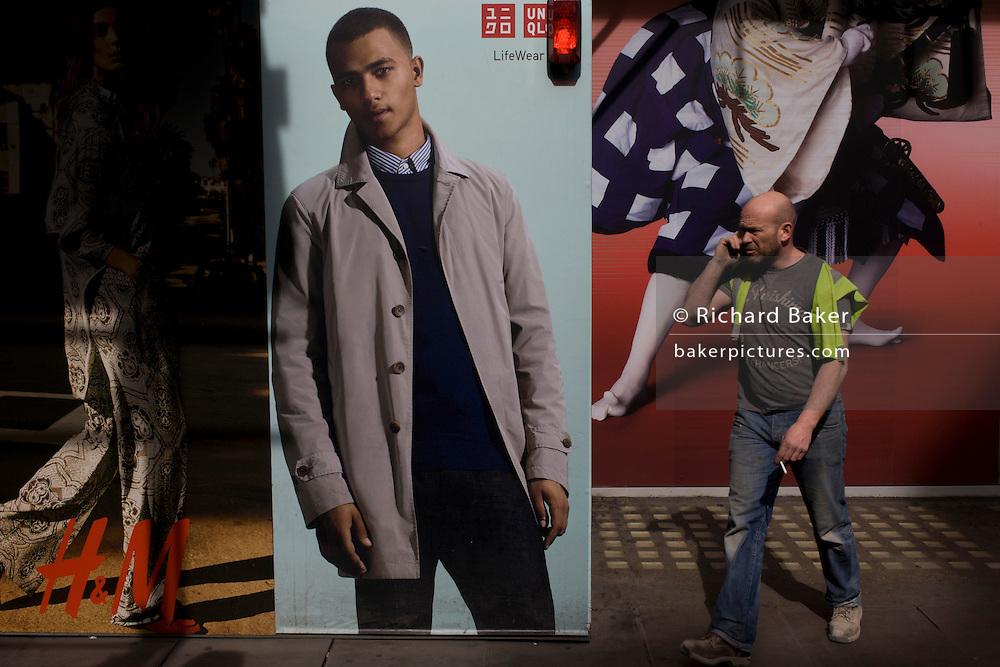 Workman walks past H&M menswear poster outside central London shop.