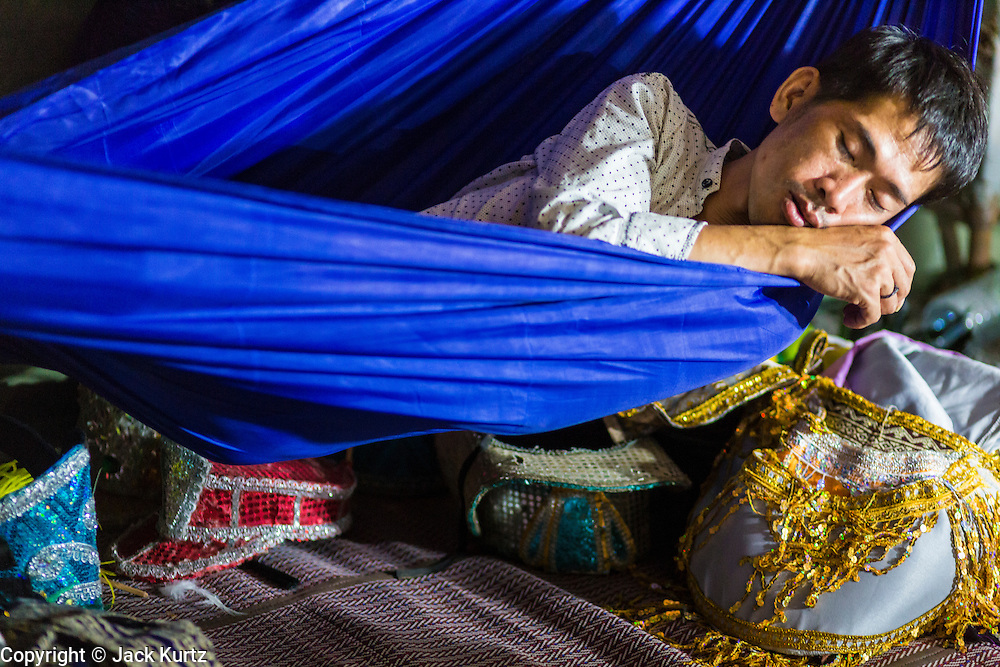 23 NOVEMBER 2013 - BANGKOK, THAILAND: A member of the crew of the Prathom Bunteung Silp troupe takes a nap during a performance in Bangkok. Prathom Bunteung Silp is one of the largest Mor Lam troupes in Thailand and travels from town to town putting on four hour shows.  Mor Lam is a traditional Lao form of song in Laos and Isan (northeast Thailand). It is sometimes compared to American country music, song usually revolve around unrequited love, mor lam and the complexities of rural life. Mor Lam shows are an important part of festivals and fairs in rural Thailand. Mor lam has become very popular in Isan migrant communities in Bangkok. Once performed by bands and singers, live performances are now spectacles, involving several singers, a dance troupe and comedians. The dancers (or hang khreuang) in particular often wear fancy costumes, and singers go through several costume changes in the course of a performance. Prathom Bunteung Silp is one of the best known Mor Lam troupes in Thailand with more than 250 performers and a total crew of almost 300 people. The troupe has been performing for more 55 years. It forms every August and performs through June then breaks for the rainy season.              PHOTO BY JACK KURTZ