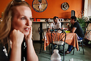 Two men talk with each other in the Gourmet Latino, a popular restaurant with temporary workers in the Leamington uptown area.