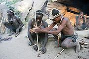 Africa, Tanzania, Lake Eyasi, Hadza men light camp fire by rubbing two sticks together. Small tribe of hunter gatherers AKA Hadzabe Tribe