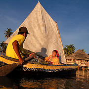 Kuna couple paddling a sailboat in Yandup. San Blas, Panama