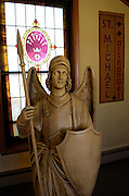 A statue of Michael the Archangel, patron saint of St. Michael Church in Iron RIver, greets guests at the church entrance.<br />