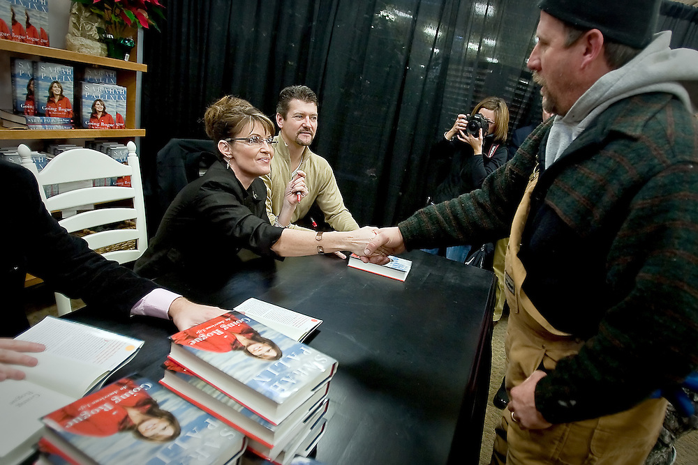 JEROME A. POLLOS/Press..Sarah Palin shakes hands with Mark Hamilton, from Post Falls, as he makes his way through the autograph line Thursday in Coeur d'Alene. Hamilton started waiting outside of Fred Meyer at 2 a.m. with hundreds of others to get a chance to meet the former vice presidential candidate.