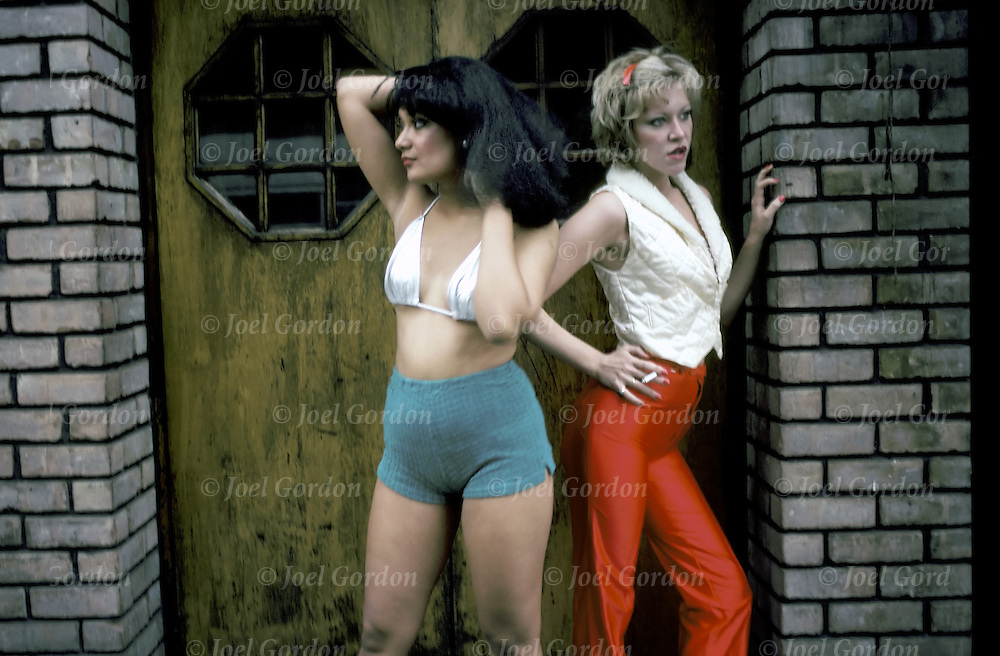 Two prostitutes, streetwalkers, women of the night, in doorway waiting to solict johns or clients who walk or drive by in New York City -  model released - © Joel Gordon   Streetwalkers are at the greatest risk for violence, drug addiction and STLs.