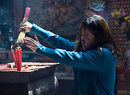 A woman lighting a bunch of incense sticks in the Chua On Lang Pagoda (Quang Am) in Ho Chi MInh City, Vietnam, Southeast Asia