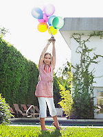Portrait of girl (10-12) holding bunch of balloons over head