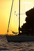A person in a hammoc onboard Amerigo, a Swan 56, in the St. Barth anchorage at sunset.
