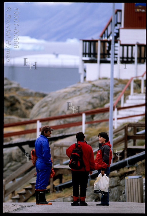Three residents stop and chat along road in the town of Uummannaq in western Greenland
