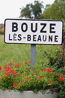 Red flowers under sign at the edge of Bouze-le-Beaune, Burgundy France.