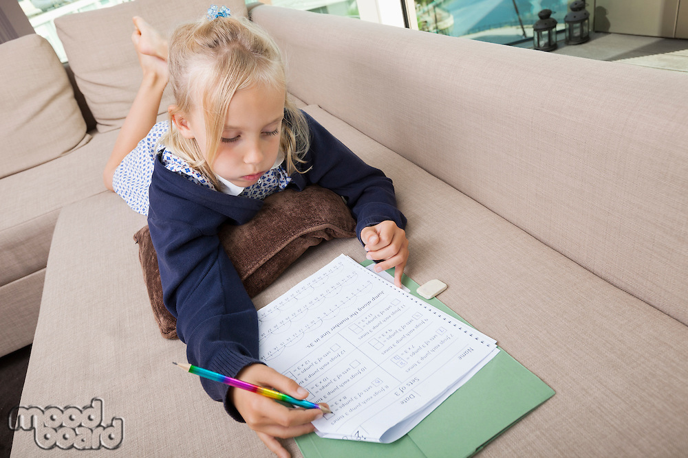 Little girl solving mathematics sums on sofa