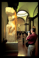 "Florence, Italy:  An unknown tourist videos the Quattro Prigioni (The Four Prisoners) sculpted by Michelangelo between 1521 and 1523.   Michelangelo's ""David"" is in the background.  Location is the Galleria dell'Accademia."